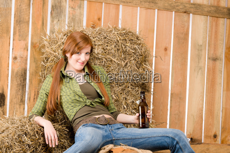 provocative young cowgirl drink beer in