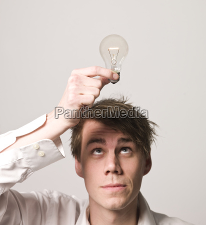 mann haelt elektrische gluehbirne ueber den