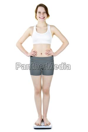 teenage girl standing on bathroom scale