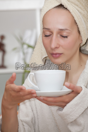 woman in bathrobe with cup