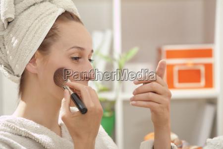 woman in bathrobe applying make up