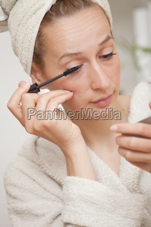 woman in bathrobe putting mascara