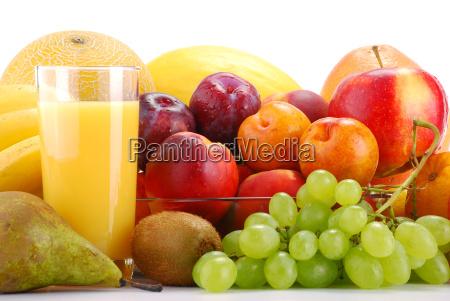 komposition mit fruechten und glas orangensaft