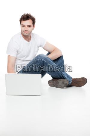 mann sitzt hinter blanck laptop