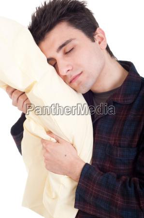 mann im pyjama halten kissen