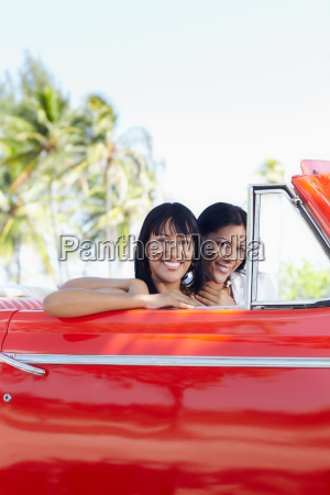 beautiful twin sisters in cabriolet car