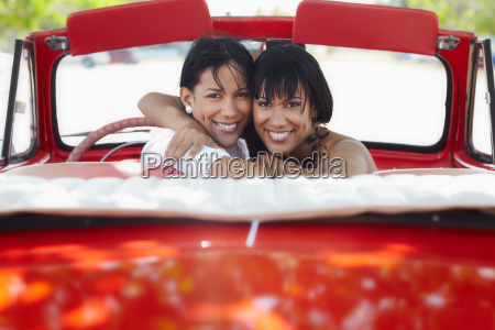 beautiful twin sisters hugging in cabriolet