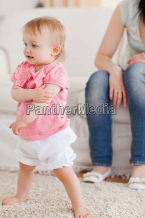 baby standing on a carpet while