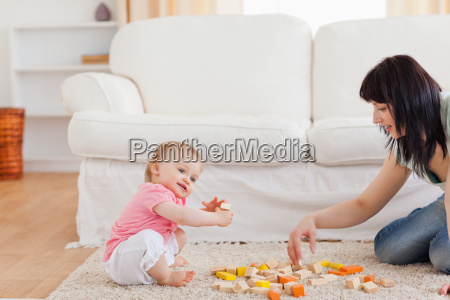 cute woman playing with her baby