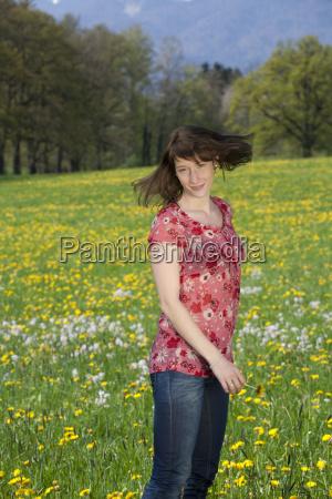 junge froehliche frau auf fruehlingswiese