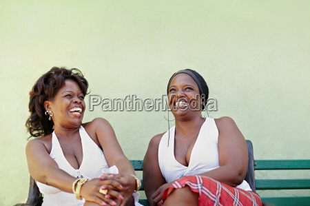 black women with white dress laughing