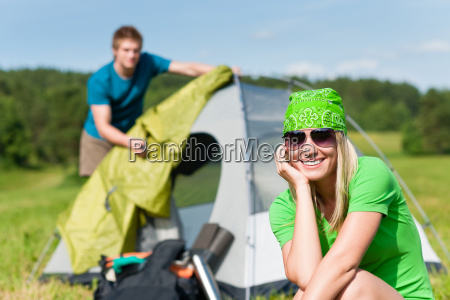 camping couple build up tent sunny