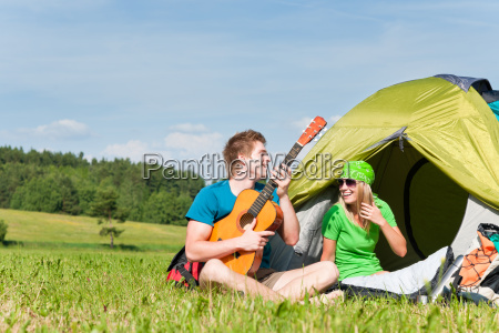 camping paar spielen gitarre durch zeltlandschaft