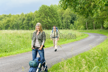 hiking young couple backpack asphalt road