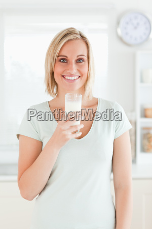 woman holding glass filled with milk
