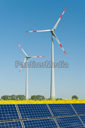 solarmodule und windkraftraeder in einem rapsfeld