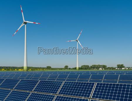 solarmodule und windkraftraeder vor einem rapsfeld