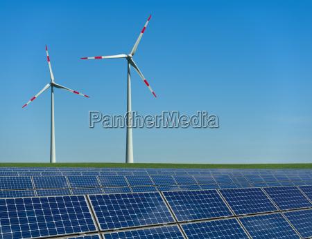 windkraftraeder und solarmodule in einem feld