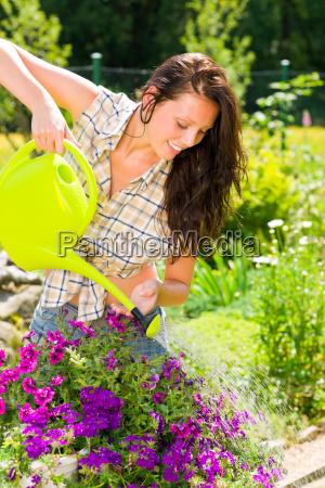 gardening smiling woman watering can violet
