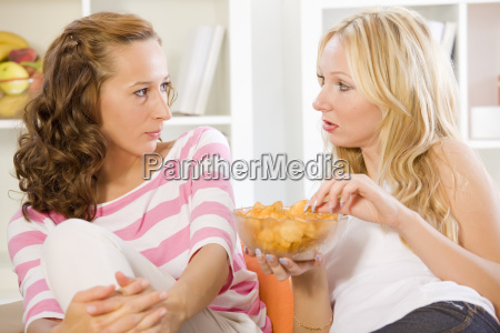 two women on sofa talking