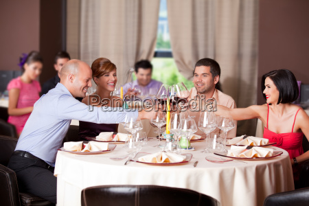 young people toasting restaurant table