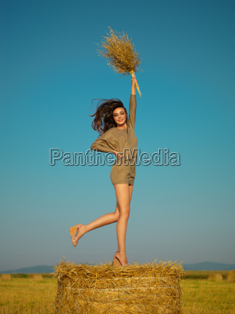 joyful young woman jumping on hay