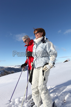 mature couple of skiers walking in