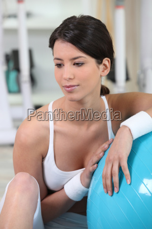 brunette crouching by gym ball