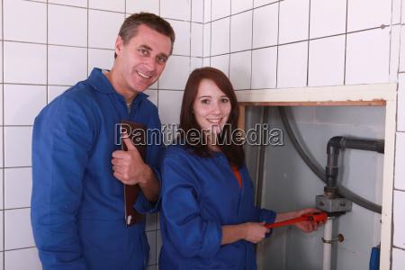 plumber and female apprentice smiling