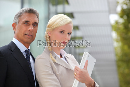 business duo outside with a laptop