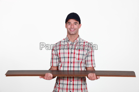 worker carrying plywood