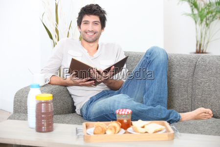 man sitting on a sofa eating