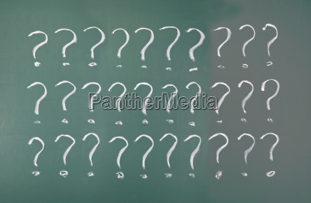 drawing question marks on blackboard
