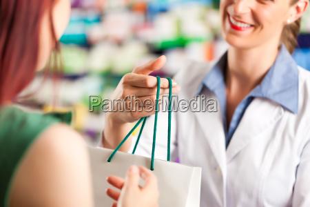 apothekerin in ihrer apotheke mit einer
