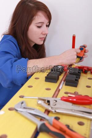 female plumber cutting copper pipe