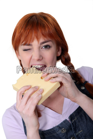 woman biting into block of cheese