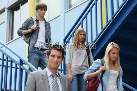 three students walking down stairs alongside