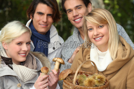 two couples gathering mushrooms