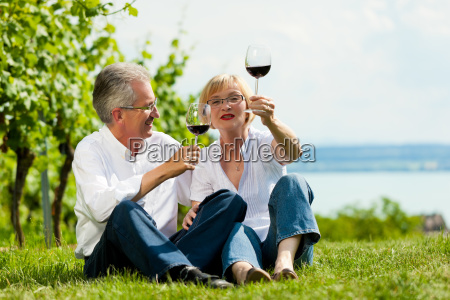 happy couple drinking wine at lake