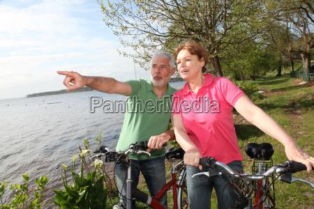 aelteres paar auf fahrradfahrt am see