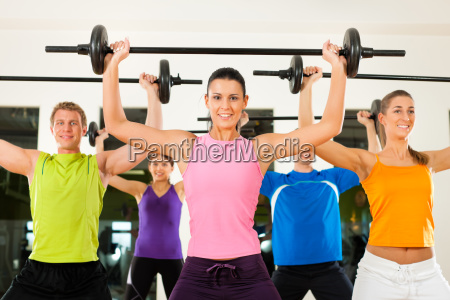 fitness gruppe mit langhantel im fitnessstudio