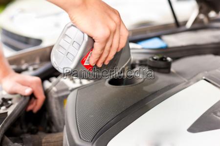 man is refilling oil in his
