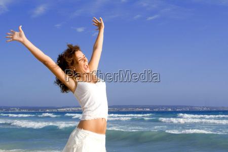 glueckliche maedchen arme auf strand urlaub