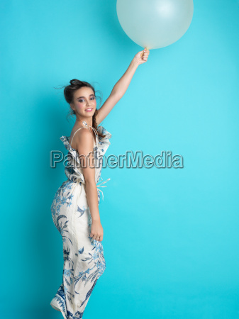 young woman white balloon blue background