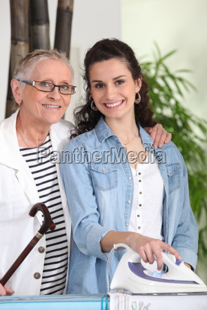 young woman ironing for an elderly