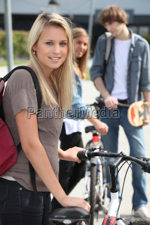 blond female teenager stood by bicycle