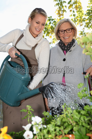 grandmother and lovely blonde watering plants