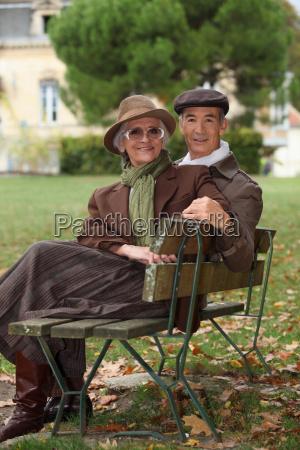 elderly couple sat on bench