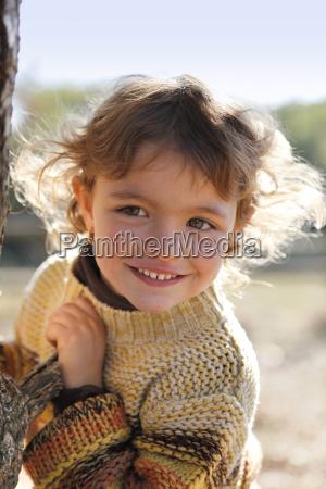 little girl stood by tree