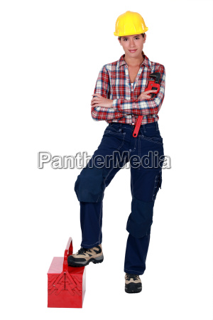 female plumber standing on white background